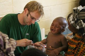 Steve tends to a child at the clinic