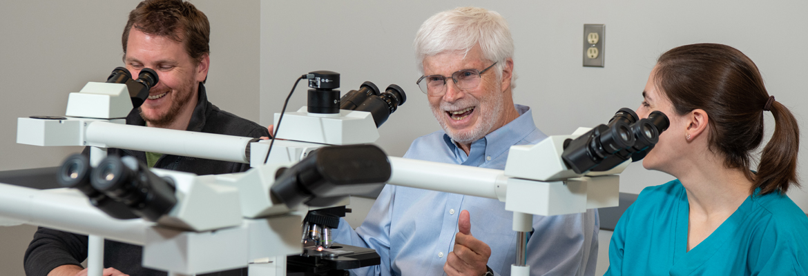 Paul Stromberg smiling over a microscope