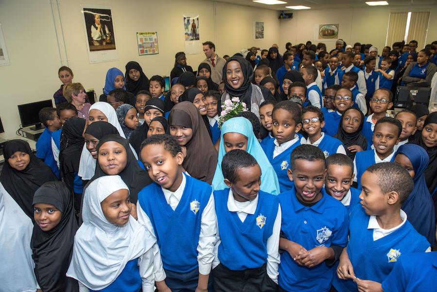 Students at Focus Learning Academy of Northern Columbus, where many youngsters in Dahir's local Somali community attend school, surround her for a photo.