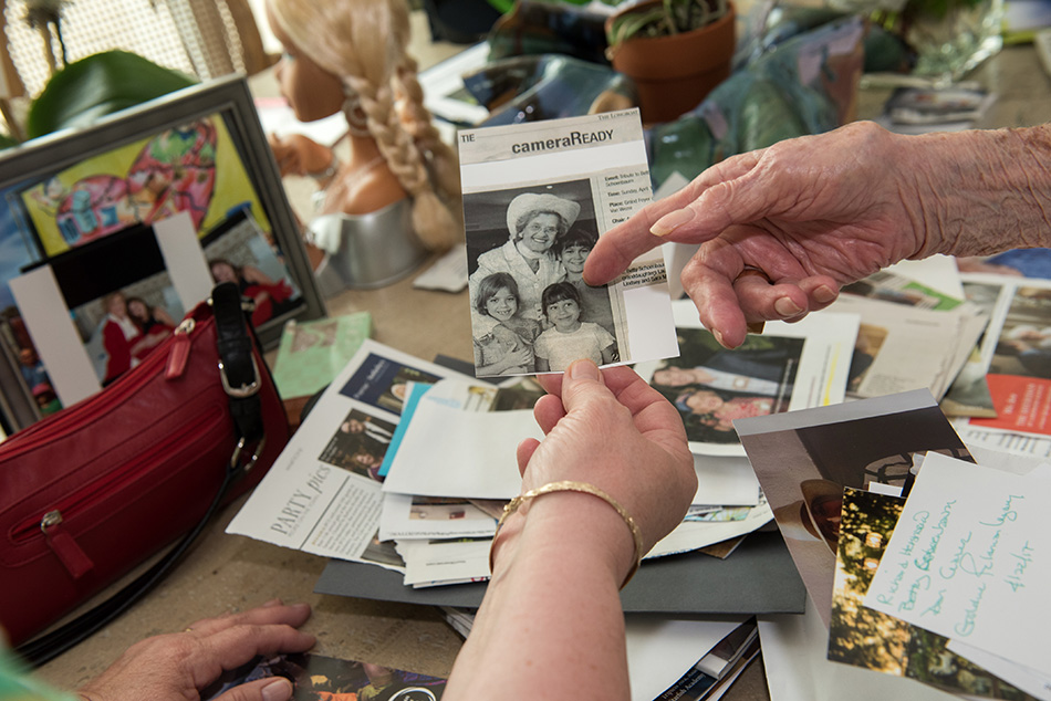 The women look through photos and newspaper clippings that chronicle Betty's 100 years of living.