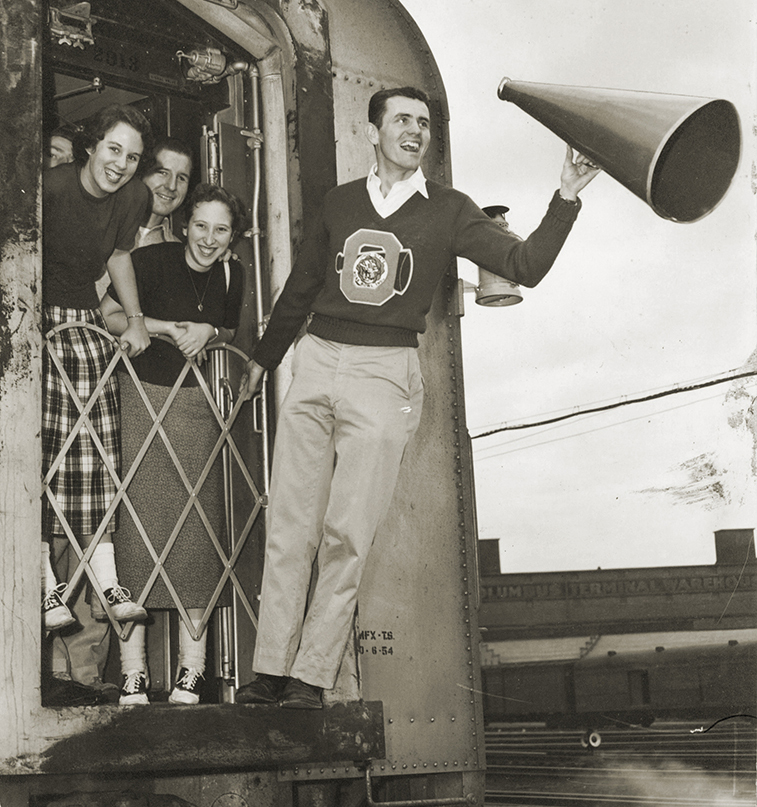 John Crawford hangs onto the back of one of six trains that carried fans to the 1955 Rose Bowl.