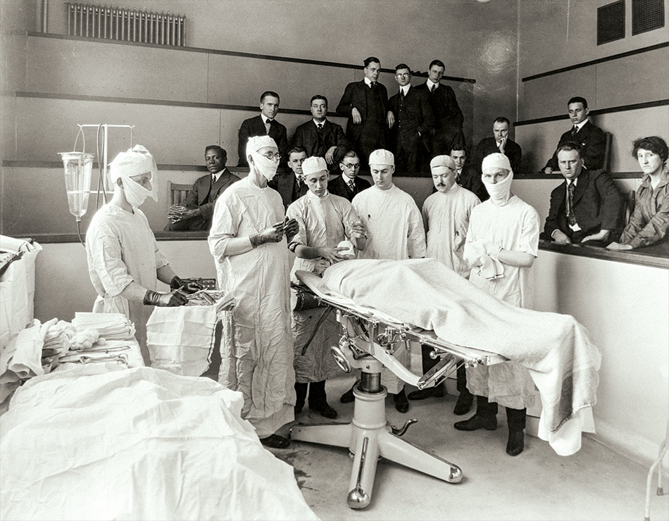 Doctors work on a surgical patient as students look on from the operating theater at Ohio State University in 1917