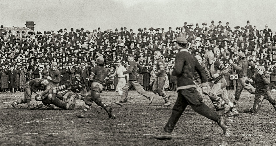 Football players clash on the field as spectators look on during a game played at Ohio State University in 1909