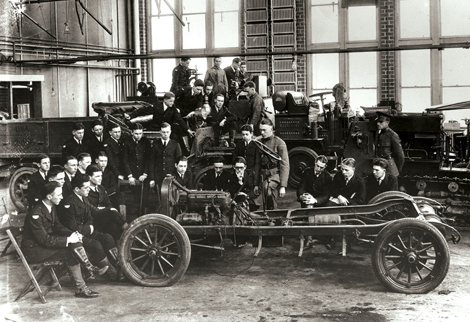 Student mechanics pose on and around an automobile chassis at Ohio State University in 1918