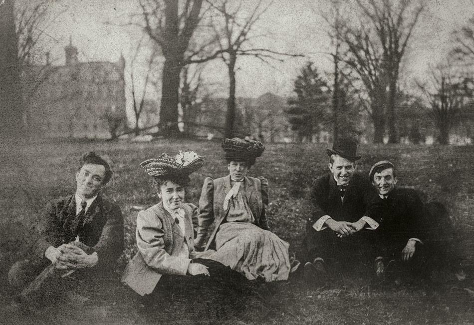 Five Ohio State University students sit together on the Oval in the early 20th century
