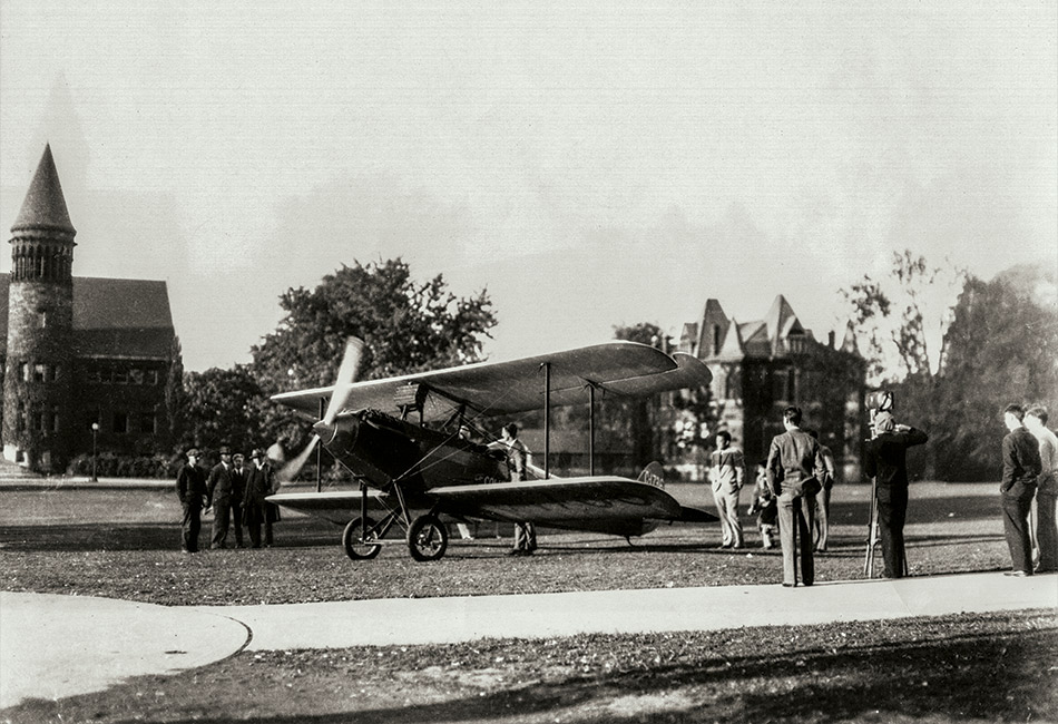 People look at a biplane that has landed on the Oval at Ohio State University