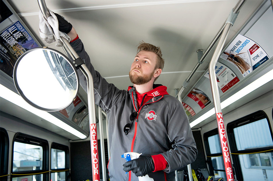 Casey Bauchmoyer '20 wipes down the interior of a campus bus