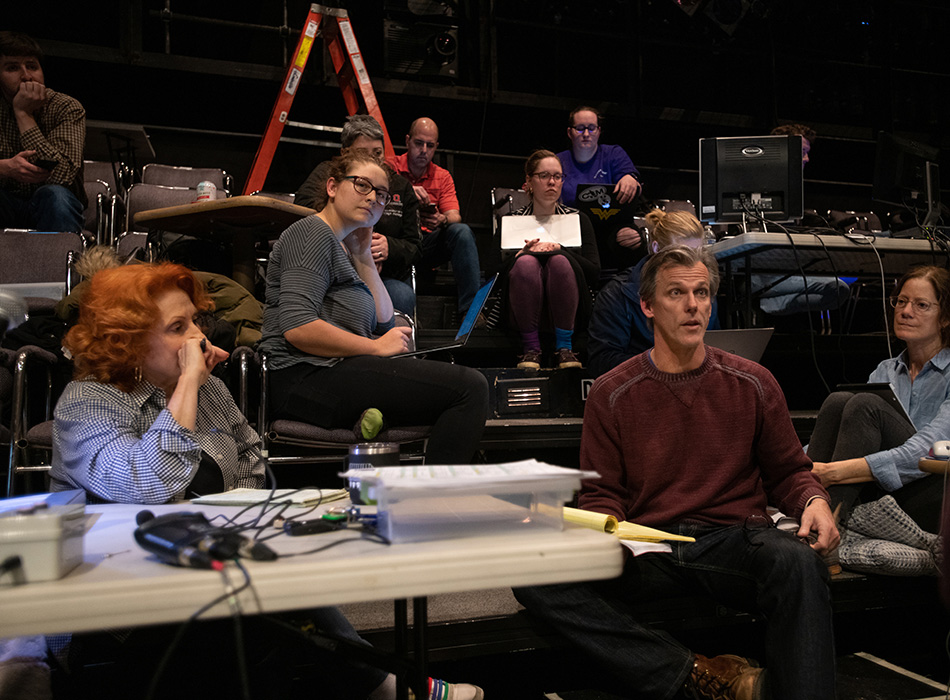 Technical personnel discuss notes following a technical rehearsal for a play