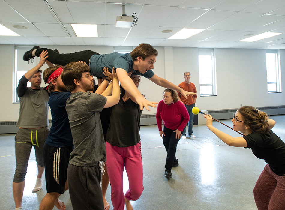 The cast of a play rehearse a scene in which an actor is held aloft as though in space