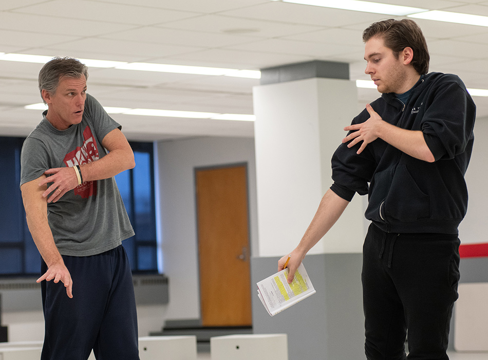 A director gives pointers to an actor during rehearsal for a play