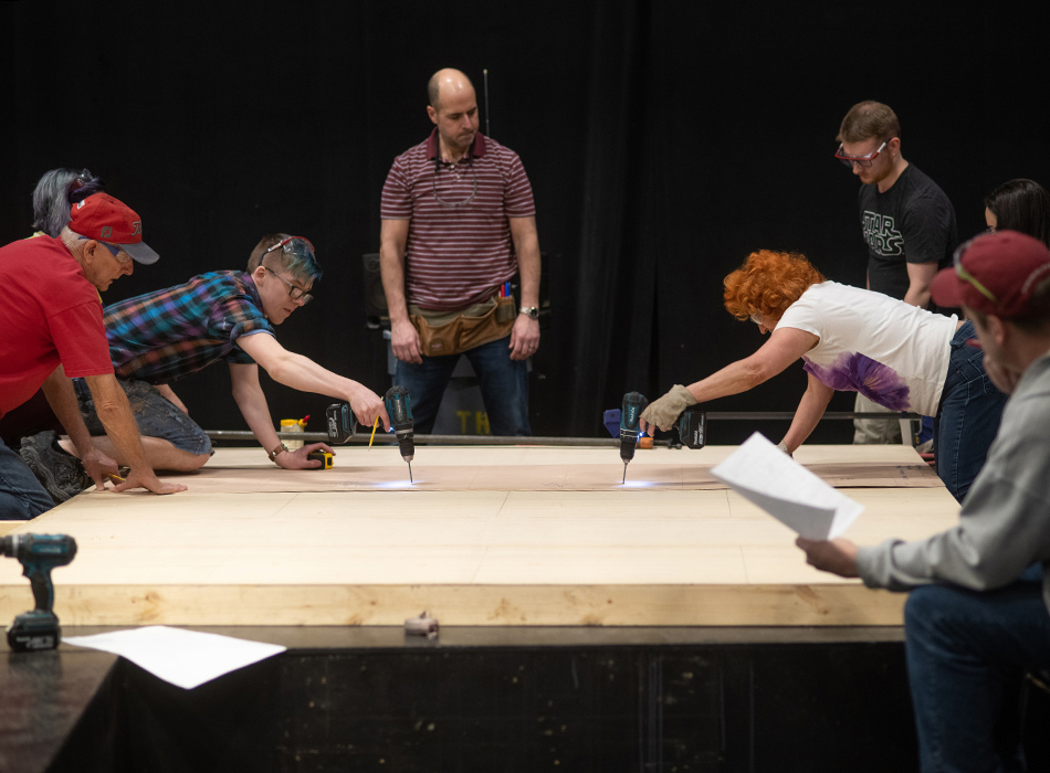 A group of people use power tools to construct a set piece for a play