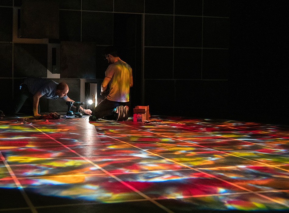 Two people work together to construct a stage for a play