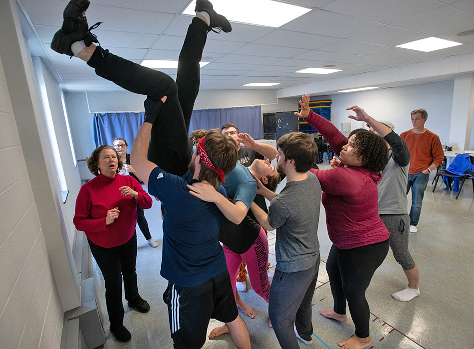 A group of actors perform an acrobatic maneuver with the lead actor in a play