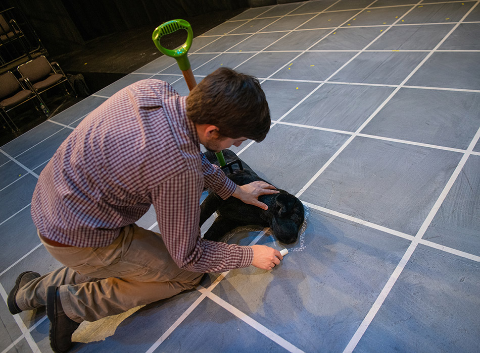 A man draws a chalk outline around a stuffed animal, a prop in a play