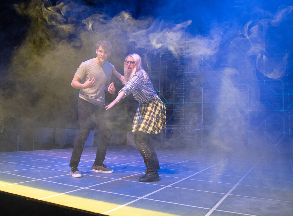 Two actors gesture in stage fog during a play