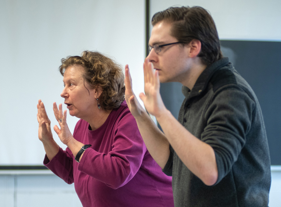 A movement director mimics a motion for an actor in a play