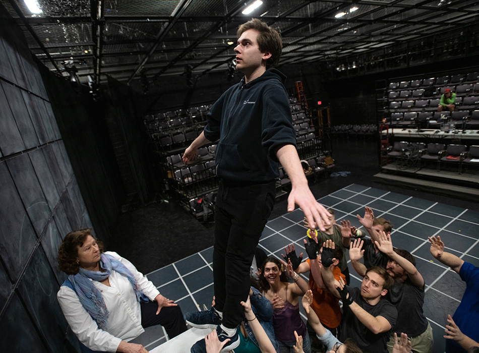 An actor prepares to rehearse a backward fall into castmates' arms