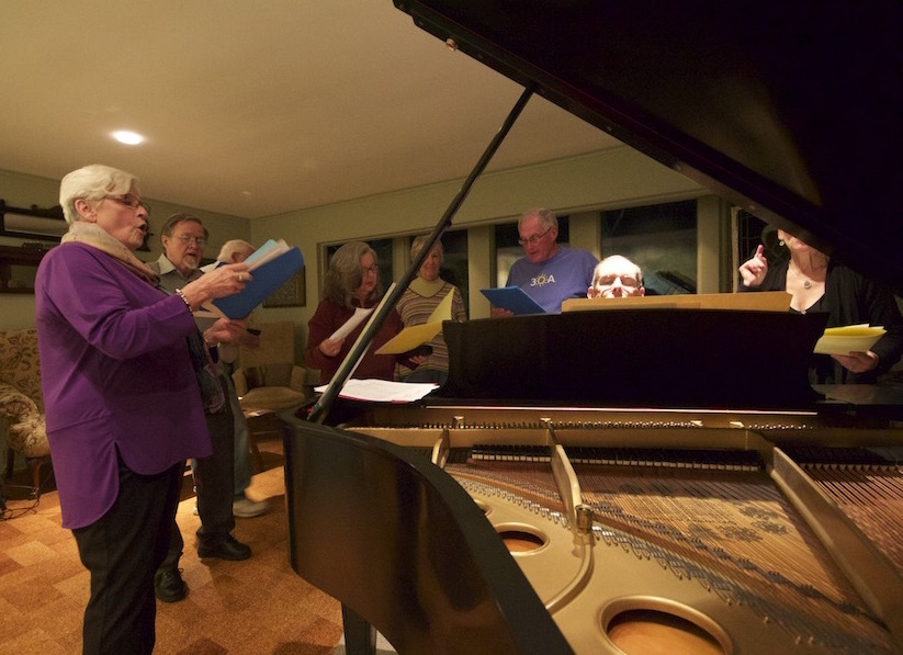 Members of the group, circa 2015, gather around the piano and their former director, Stephen Jacoby, to sing some of the tunes they performed 50 years ago. (Photo by Alex Conrath)