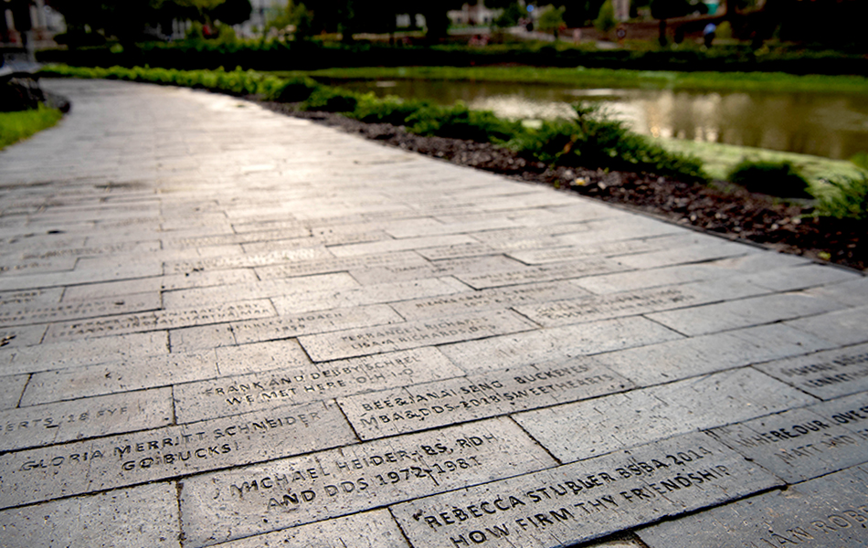 A view of engraved bricks paving a walkway adjacent to Mirror Lake at The Ohio State University