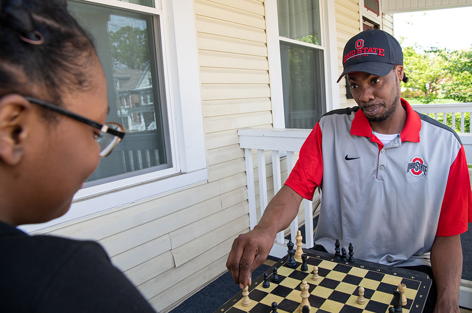 A man and his daughter play chess on their front porch.