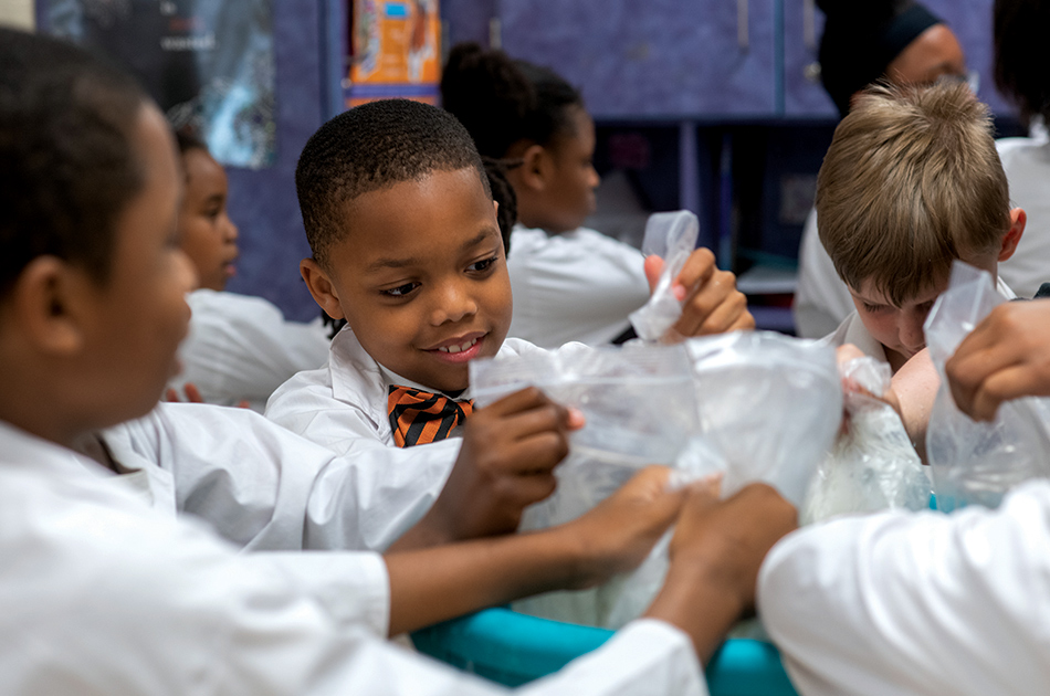Young children conduct a science experiment in school