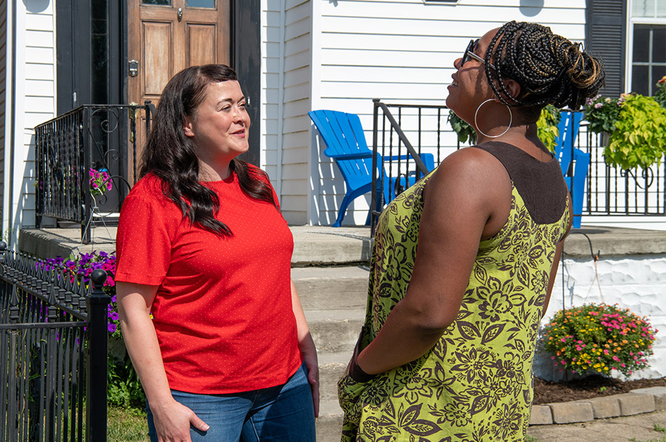 Two women chat outside a house in Columbus, Ohio.