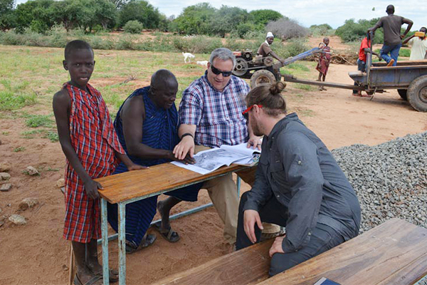 Two researchers from Ohio State sit at a table with two people who live in Marwa, Tanzania