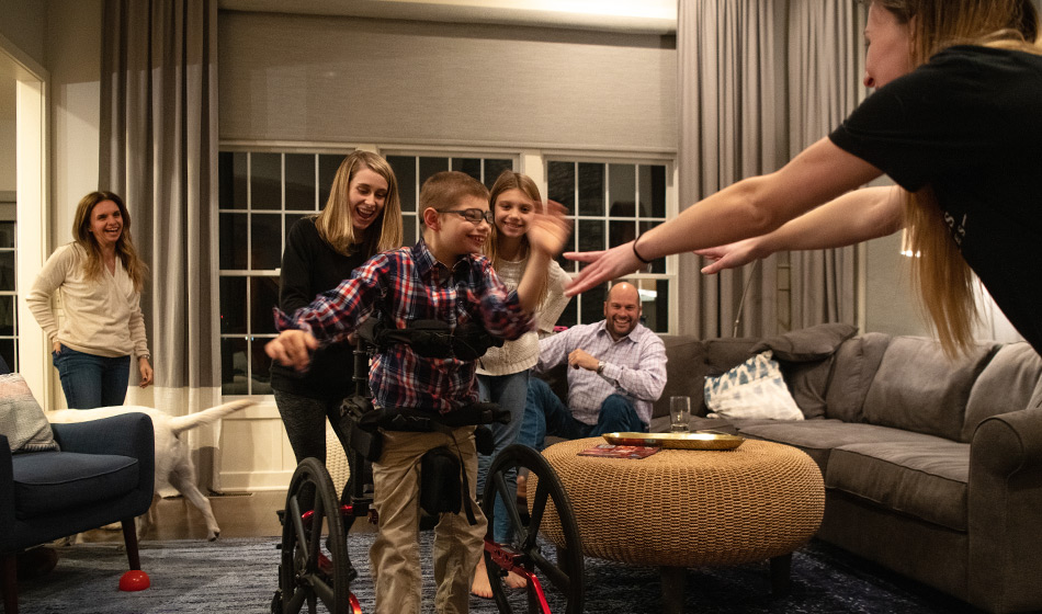 Five relatives and friends cheer on a young boy as he learns to use a walker