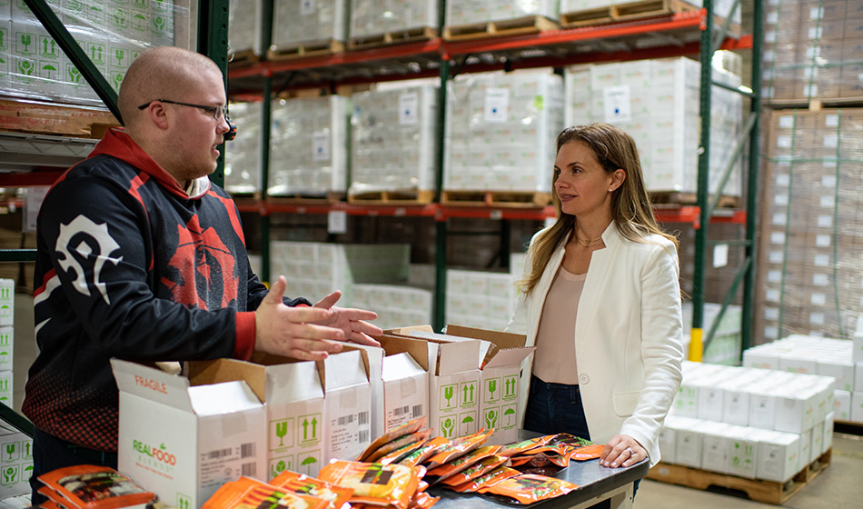 A man in a blue and orange hoodie speaks with a woman in an ivory jacket on the floor of a warehouse whose shelves are stacked with boxes