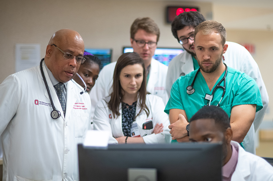 A doctor and medical students gather around a computer monitor
