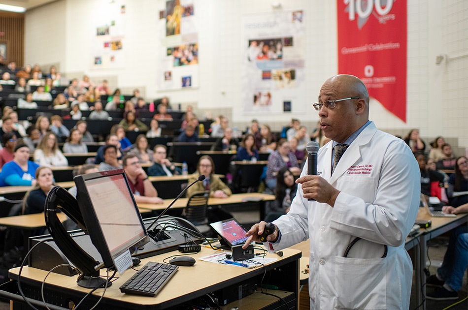 A doctor holding a microphone speaks to students in a large lecture hall at The Ohio State University