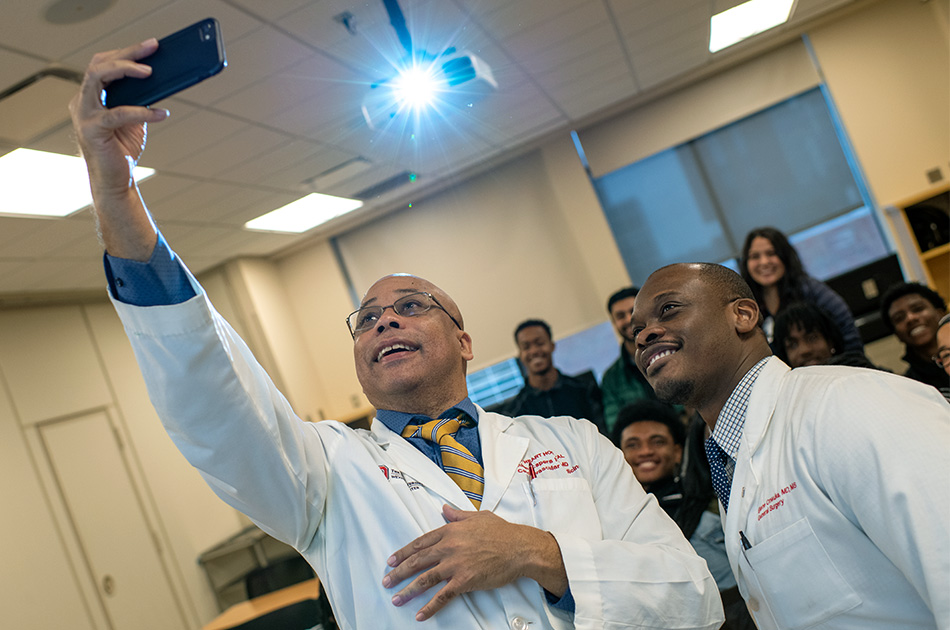 A doctor snaps a smart-phone selfie with a group of students