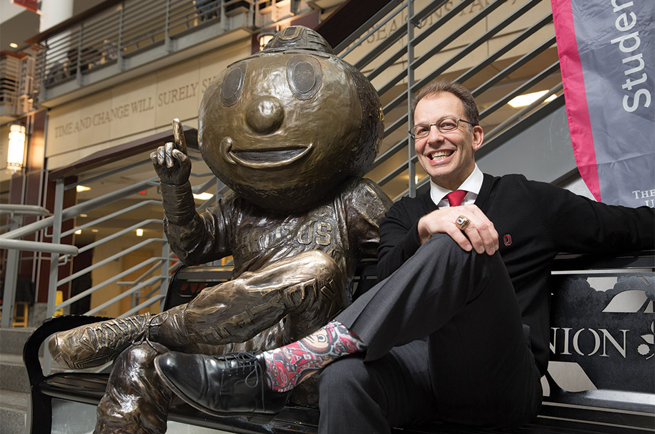 A man sits next to a bronze statue of Brutus Buckeye