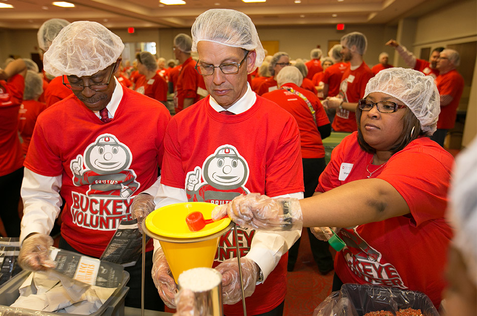 Three people work to pack meals during a benefit event