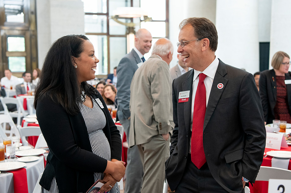 A man and woman in business dress chat at an event at the Ohio Statehouse