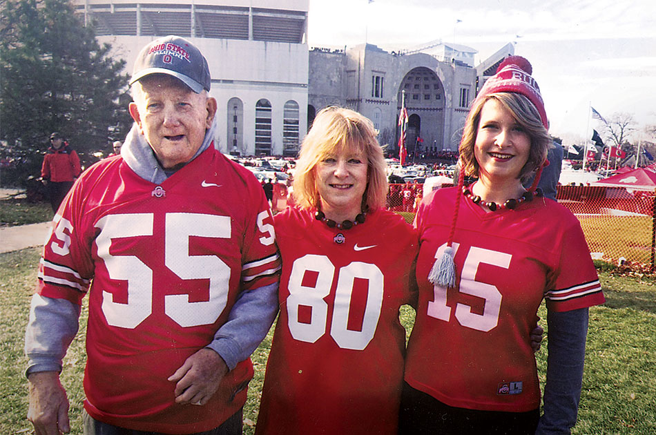 A father and his adult daughter and granddaughter pose together for a photo outside Ohio Stadium