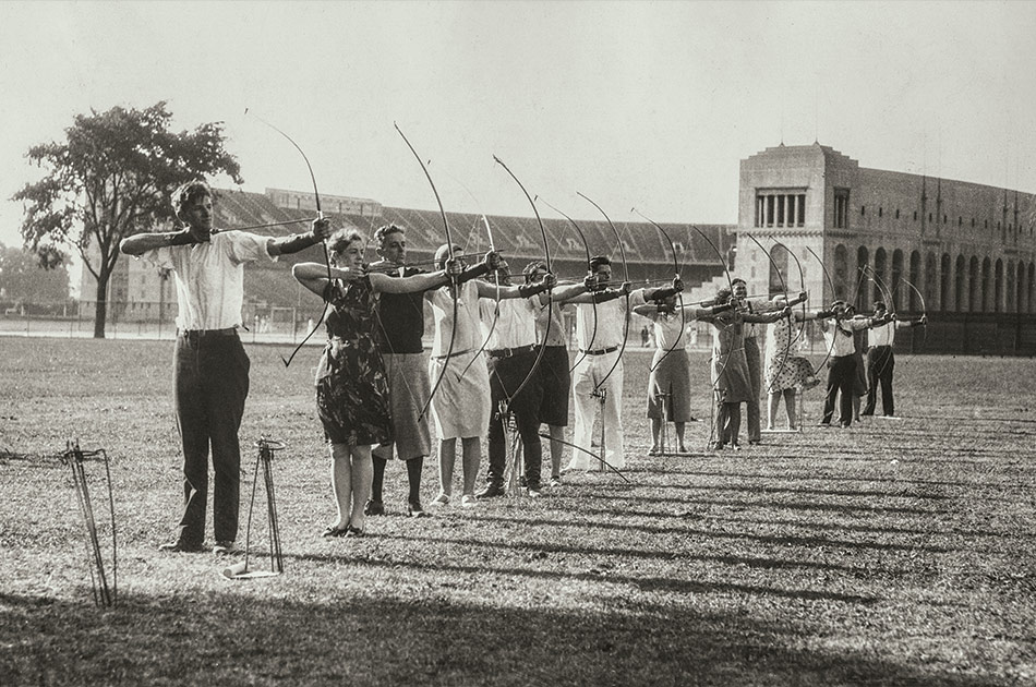 Ohio State University students aim bows and arrows during archery practice outside Ohio Stadium