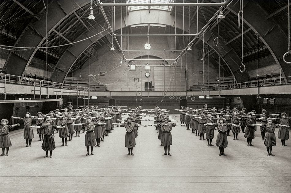 Female students at Ohio State University perform calisthenics in a wide-open armory room