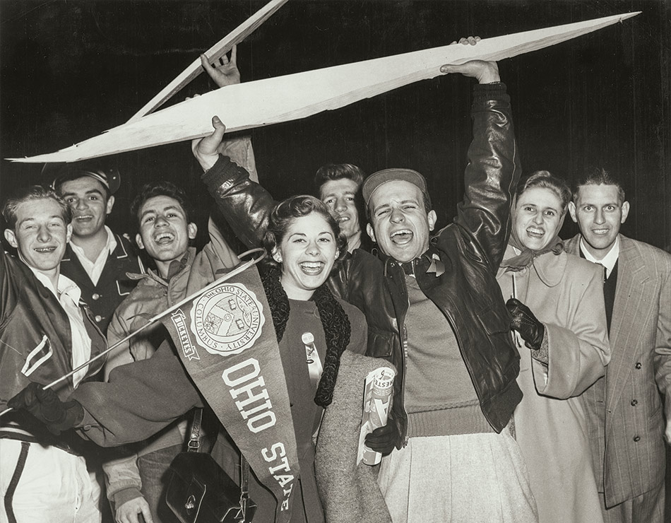1940s-era Ohio State University students wave pennants, hold a chunk of a football field goalpost and cheer