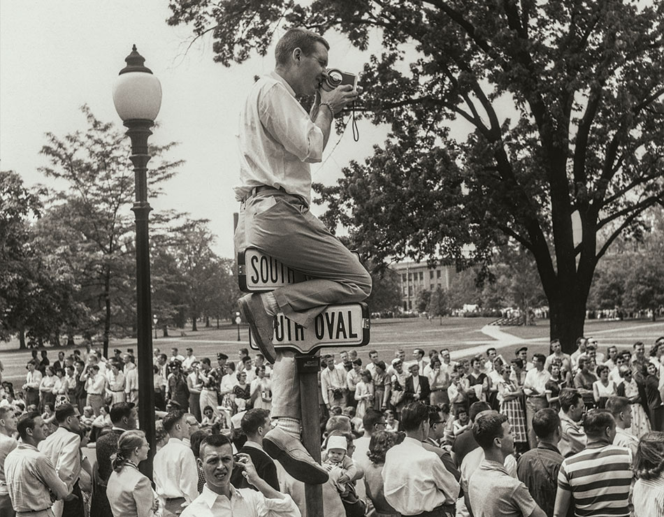 A man perched on a street sign, shooting film as he looks over a crowded Oval at The Ohio State University in 1955