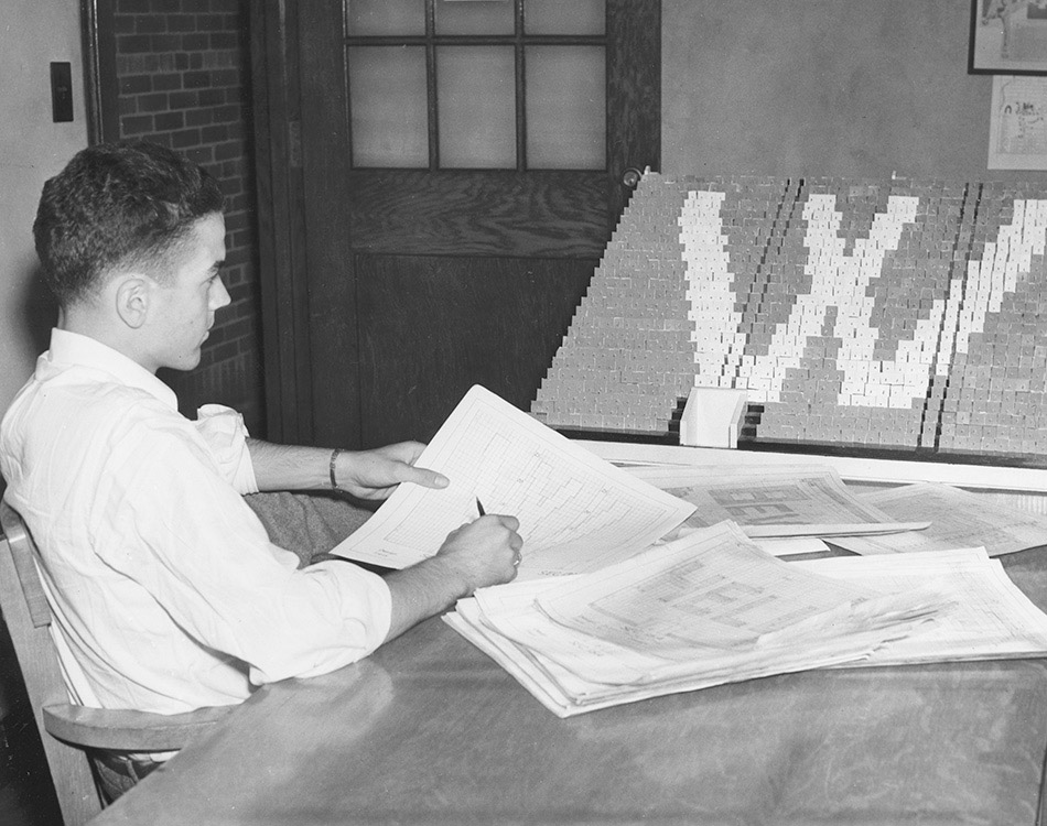 A Block O member uses a 3-D model to chart a W-shaped card stunt for the student cheering setion.