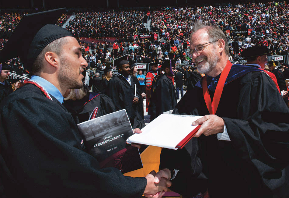 Handing a diploma to a graduate