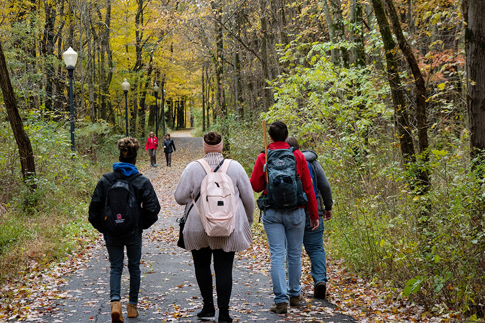 Students walk through a wooded area