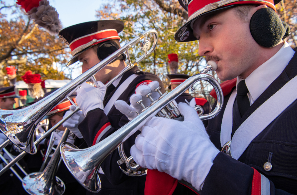 Two members of The Ohio State University marching band, clad in earmuffs and gloves, blow on their brass instruments in the Macy's Thanksgiving Day Parade on Nov. 22, 2018.