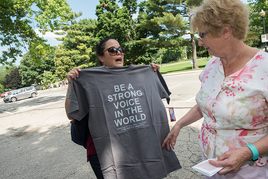 Angelica Gutierrez Klingsmith holds up a T-shirt shirt she bought in Hagerty Hall, where she studied foreign languages, to reveal an empowering message that she works to embody as a teacher.