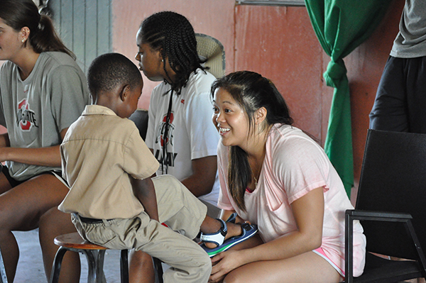 Gymnast Michelle Burns chats with a Jamaican boy.