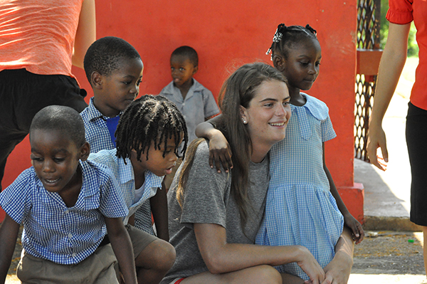 Kylie Randall of women's volleyball hangs out with new friends in Jamaica.