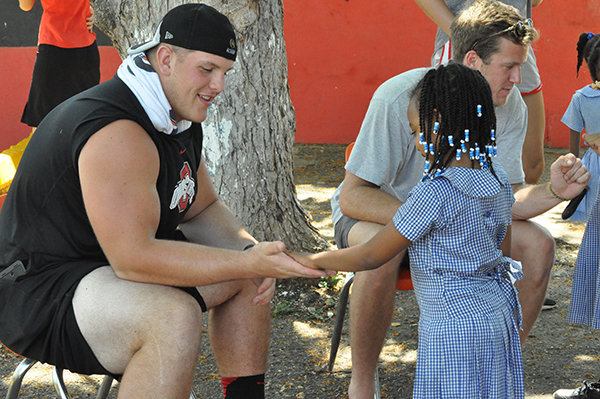 Football player Billy Price high-fives a Jamaican girl.