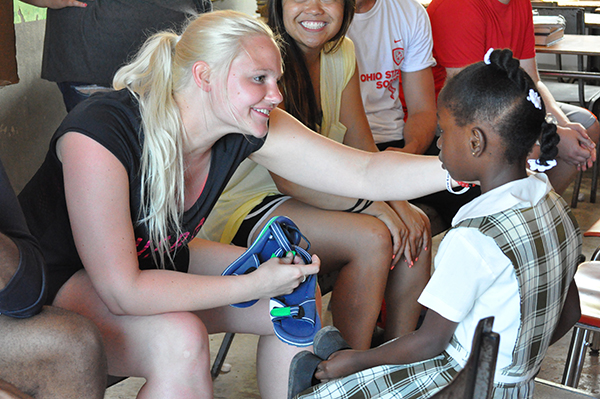 Pistol team member Liz Buerling fits a Jamaican girl for shoes.