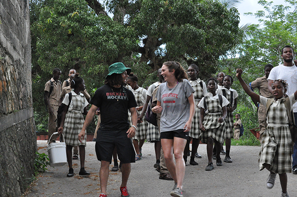 Hockey player Christian Lampasso, left, and soccer player Lindsay Agnew head a procession in Jamaica.